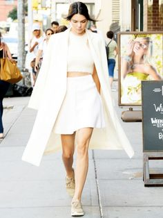 Kendall Jenner wears a white crop top, white miniskirt, neutral Nike sneakers, and a white coat