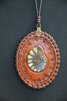 Chambered Nautilus Fossil Laced Pendant.  Set by hand in rich saddle tan leather, hand tooled, hand laced for that human touch. on Etsy, $73.00