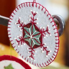 Beginning sewerswill have fun creating this simple circle-shape ornament; adorn with snowflakelike designs or other seasonal images, such as trees and candy canes. Start by cutting two circles of felt; attach together using a blanket stitch. Use contrasting felt colors to add designs; here, a star shape is overlaid onto a small hexagon, and straight stitches and French knots provide decorative elements. Create a hanging loop with a longer piece of knotted thread.