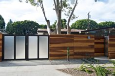 The gates are made from 2×4 lumber with tempered mistlite glass panel inserts. The gate parts in the middle and slides behind the redwood fence.