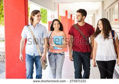 Attractive Hispanic college students walking together and talking on a school hallway - stock photo