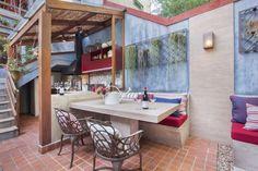 Imagem de Os bancos, a mesa de refeições e a bancada da pia foram produzidos em concreto, para conferir um toque mais rústico. A estrutura de madeira ganhou cobertura de vidro e bambu para bloquear o sol.