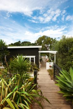 Exterior An original take on the beach-shack style, this 1950s four-bedroom weatherboard cottage sports stained-black...