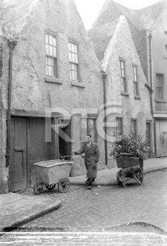 A man walks past two wicker hand carts outside terraced houses on Marrowbone Lane, Dublin city, in 1952 or 1953. The street is cobblestoned. *Note the area of negative damage at the bottom of frame.* Collection RTÉ Johnson Collection Photographer Johnson, Nevill