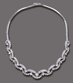 A DIAMOND NECKLACE, BY CARTIER   The front composed of a series of graduated circular-cut diamond swags, enhanced by square-cut diamonds, to the circular-cut diamond backchain, mounted in platinum and 18k white gold, 13¾ ins., with French assay marks and maker's marks  Signed Cartier Paris