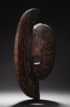 Bobo (Burkina Faso)Mask with Crescent shapeWood, pigment, abrus seeds, fiberHeight: 15 inches Width: 5 ¾ inches Depth: 8 7/8 inchesThis is a mask of hemispherical shape, with a large crescent-shaped, flat vertical extension bisecting the face. The eyes, beside this blade-like feature, are surrounded with red abrus seeds. 3/4 view