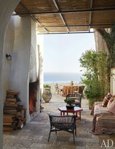 An outdoor fireplace warms this stone terrace at the Malibu home of designer and antiques dealer Richard Shapiro, who furnished the plein-air space with rattan and wicker chairs and striped fabrics.