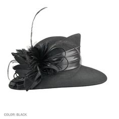 Designed with an asymmetrical crown and brim, the wool felt dress hat is trimmed in a sheen a satin hatband, tonal soft feathers, a wool felt flower and satin ribbon curls.
