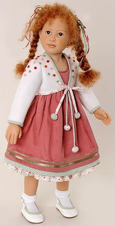 This Caucasian doll has red human hair and mouth blown brown glass eyes. She wears a short sleeved terracotta coloured cotton dress with silk laces around the bottom and a green and white checkered trim with an attached white cotton shift dress with a flower-printed flounce. On top of that she wears a long sleeved felt vest with colored felt applications that has a loop to close with bobbles at the end. She also has white leather shoes with light green trim and white socks.