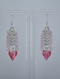 $62.50, A Swarovski Wild Heart Crystal dangles from a length of box weave chainmaille. Surrounded by pink seedbead columns, these pretty earrings are loose and lively.