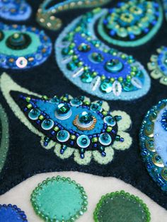 ARTIST a little bit of just because  TITLE Dream Fragments Closeup 3    Each paisley was individually beaded/sequined and then stitched to the blue backing. The blue was then quilted to the cream (bit hard to see in these photos, but the quilting makes each of the paisleys pop up from the background). The circles around the outside were then stitched directly onto the background and then beaded. The entire piece is backed with felt and 'signed' in stitching on the back.