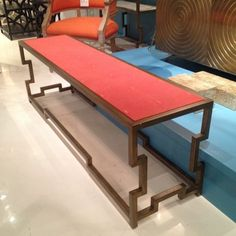 "A very Hollywood Regency cocktail table/bench, with a bit of a twist: the shagreen-look top is a bright coral shade of ""tangerine"", a nice complement to the gold tone metal Greek Key base. Mr. Brown, Interhall"