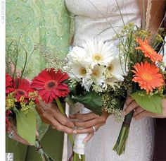 bouquets of gerbera daises, sea grasses, and wildflowers and marked the ceremony spot with a woven torch overflowing with wine-color tulle, gerbera daisies, and greenery.