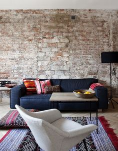 Raw brick wall, navy sofa and tribal inspired rugs and textiles everywhere