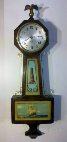 An unique banjo clock by Sessions Clock Company featuring, an octagonal head, nautical scenes behind glass, and a large eagle finial.