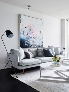 Living room: pale grey sofa, scatter cushions, pastel painting artwork, black reading lamp, dark floorboards, light grey low-pile rug, white round marble nesting coffee tables