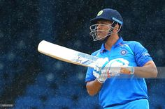 Mahendra Singh Dhoni of India looks on as rain falls during the match between West Indies and India as part of the Seagrams Royal Stag Mega Cricket Cup 2017, One Day International Series at Queen's Park Oval on June 23, 2017 in Port of Spain, Trinidad & Tobago.