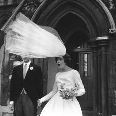 The veil of newly-wed bride Eileen Petticrew flies up in a gust of wind as she poses for photographs with husband Robert Greenhill outside St. John the Evangelist Church, Notting Hill, London, 1965.