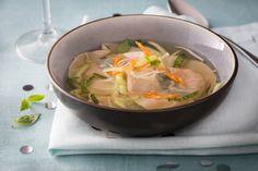 Des ravioles de Saint-Jacques garnies d'une feuille de basilic thaï, servies dans un bouillon de crustacés parfumé au combava et agrémenté de carottes jaunes, de chou pak-choï, d'enoki et de pousses de soja.