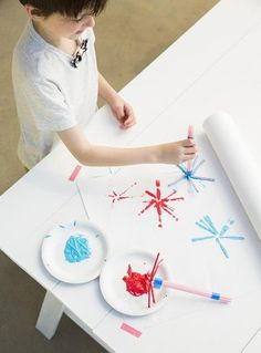 For fun fireworks, cover a table with kraft paper or drawing paper (the kind that comes on a roll). Tape 7 bendable straws together with their ends arranged into a starburst. Spread washable red and blue paint on paper plates, then dip and stamp the starburst onto the paper. When the first color is dry, add the second color.