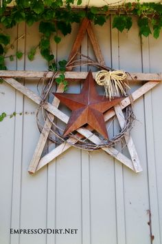 Turn plain, boring fences into fun, upcycled works of art with these craetive ideas. Make a rustic garden art star from wood scraps, a wreath, and a tin star. Come visit the Empress of Dirt for more ideas.