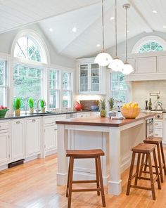 Light bounces around the walls (in Benjamin Moore's Palladian Blue) and on the cabinets (in White Dove) in this bright kitchen, thanks to the many windows, including the half-circle window above the sink.