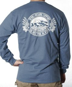 This Long Sleeve Men's Tee is made with 100% preshrunk cotton and features our white Traditional DBC logo on the back. It reads DENALI BREWING / TALKEETNA, ALASKA on the front. Available in Burnt Orange, Indigo Blue and Black.