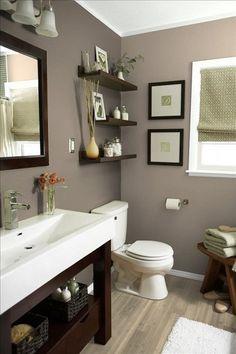 Dans cette salle de bain la couleur taupe tapisse les murs tout en s'accordant avec les éléments en bois foncé et blancs. Une harmonie de couleur originale pour la salle d'eau d'habitude froide, qui s'imprègne cette fois d'une ambiance chaleureuse et douce.