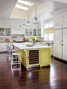Oak flooring in an ebony stain anchors this elegant kitchen and provides contrast to the white walls and cabinetry.