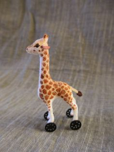 Just like the big version from the famous German toy maker, this miniature plush giraffe is ready for playtime with the smallest dolls. He stands only 1 3/4 tall. Hand furred, with glass eyes and wooden wheels that turn.   All of my creatures are recreated from my original carvings and hand finished individually. Like any handmade product they will have variations. They would be happiest with adult collectors and are not toys intended for children.