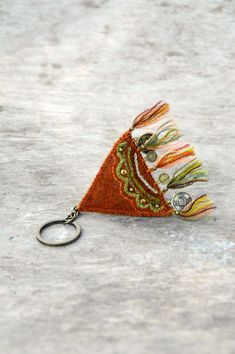 Rustic orange woolen keychain with embroidery and brass by Mioltu, €28.00