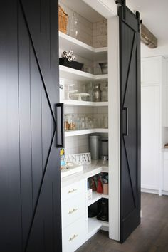 This farmhouse pantry is stylish and functional! My inspo behind the pantry was a European cafe mixed with rustic touches. This look was accomplished by mixing a subway tile backsplash from the floor-to-ceiling, gold brushed pulls and shallow shelves paired with barn doors, rustic signs and farmhouse containers. Check out all the details and shop all my favorite links. | SBK Living