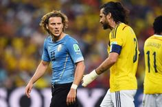 Diego Forlan of Uruguay and Mario Yepes of Colombia clash during the...