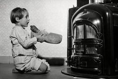 : Meisje zingt sinterklaasliedje bij de kolenhaard met een klomp met een wortel en stro in haar hand. Nederland, 1959.  English: Dutch girl singing song for Saint Nicholas. The Netherlands, 1959.