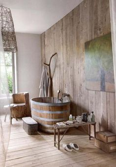 salle de bain rustique au charme naturel avec un lambris mural en bois, baignoire ronde en bois et métal et meubles en bois