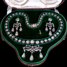 Beautiful suite of diamond jewellery set 'en girandole' and comprising a graduated diamond riviere necklace with detachable brooch-pendant of foliate scroll design and a pair of earrings.   English circa 1830