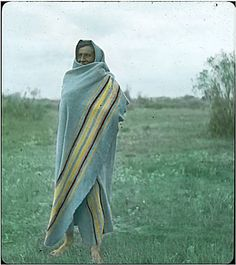"Early 1900's  	Crow person standing wrapped in blanket in Montana.  Hand written on edge of slide, ""It was customary to take a morning dip in the stream."""