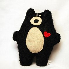 Handmade plush fleece bear measures 12.5 x 10.5. Created with black faux fur. He has a tan tummy patch, tan muzzle, button eyes, and a red heart on his chest.