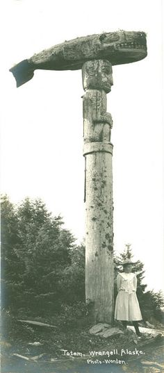 """"""" Totem Wrangell, Alaska"""" by Worden, circa 1900. A young Caucassian girl in Victorian dress standing next to a large killer whale totem in the village Kaachxan.aak'w ( translated as Little Lake Accessible to the People )"""