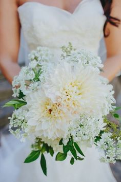 This bouquet is dahlias and Queen Anne's lace, which is a wildflower.  Not sure what the greenery is.
