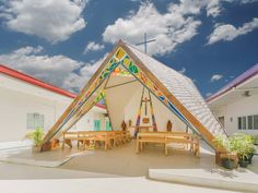 The Chapel of St. Benedict and St. Scholastica, situated in Pambujan, Philippines, is a simple, colorful structure that accommodates parishioners under a wide-open sky.