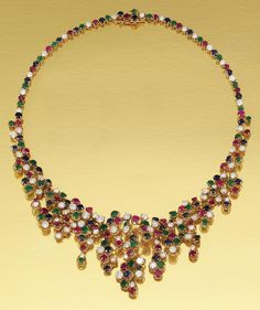 GEM-SET AND DIAMOND NECKLACE, BOUCHERON. Designed as an abstract cascade set throughout with circular-cut rubies, sapphires, emeralds and brilliant-cut diamonds, length approximately 420mm, signed Boucheron and numbered, maker's marks, French assay marks.