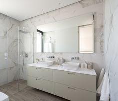 Baño de vivienda en Ibiza, diseñado por Natalia Zubizarreta Interiorismo. Mueble de baño en madera lacada de Codisbath con lavabos sobre encimera de Villeroy&Boch y grifería de pared de Noken. Espejos retroiluminados. Paredes en azulejo mármol. Baldosa porcelánica imitación madera Floorgres. Mampara a medida de Profiltek. Ducha a medida integrada en pavimento con grifería Noken. Focos integrados en techo. Foseado perimetral en techo retroiluminado.