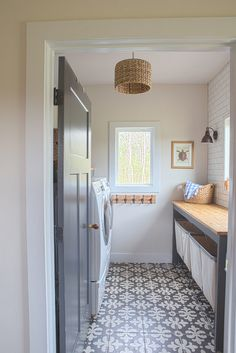Farmhouse laundry room with grey interior door, grey custom folding doors and cement floor tile. Grey interior door paint color is Blackened by Farrow and Ball #BlackenedbyFarrowandBall Sharon Barrett Interiors