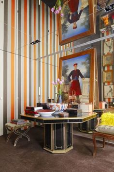 A Paris pied-à-terre designed by Sig Bergamin showcases a sophisticated gallery with walls covered in a fall-like brown and white fabric by Romo. The carpet is by Stark and the artworks above a 1970s bronze console are mostly Brazilian.