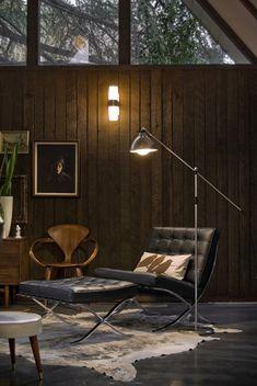 Barcelona Chair, Ottoman, Cowhide Rug, Wood Paneling, and Modern Chrome Lighting, combine to create a Modern Dutch Cabin.