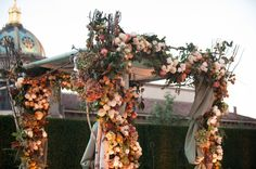 The birch framed Chuppah supported thick Magnolia and Eucalyptus garlands laden with clusters of Bosc and Forelle Pears, pomegranates, persimmons on the branch, golden raisin grape clusters, antique Hydrangea and Vendela roses.