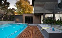 jardin-avec-piscin-forme-rectangulaire-revetement-sol-bois-mur-verre