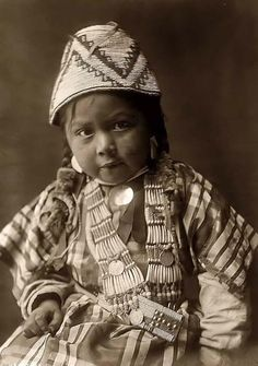 Above we show a vital photo of a Wishham Child. It was made in 1910 by Edward S. Curtis.    The illustration documents a Wishham Indian girl, three-quarter length, seated, wearing basket like hat, cotton plaid dress, shell beads decorated with silver dollars.