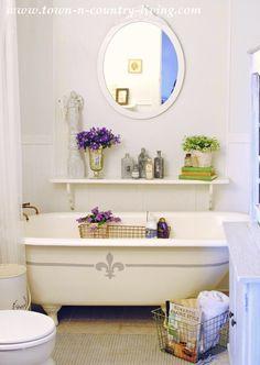 Clawfoot tub in a Farmhouse Bathroom. A fleur de lis gives it a French country touch.